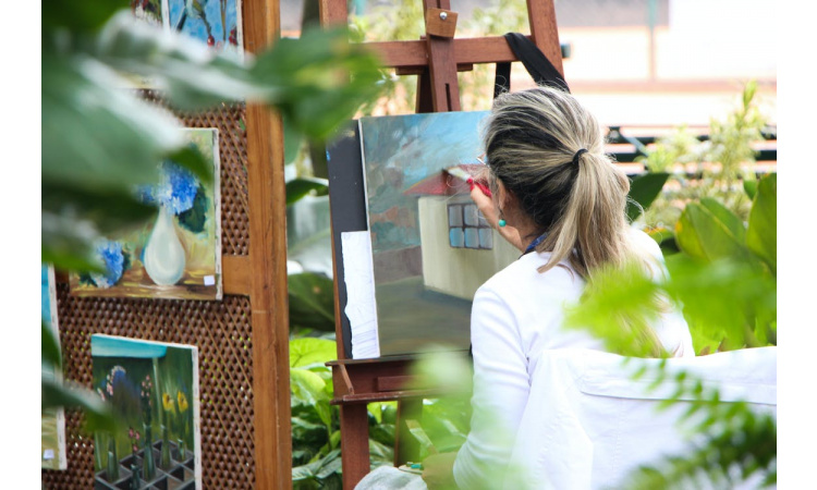 A woman painting in the garden